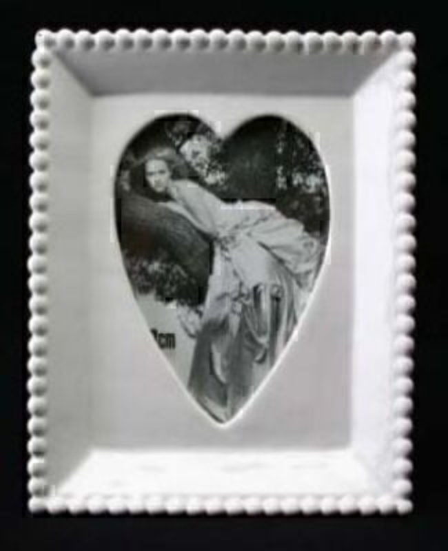 White ceramic photo frame with 'beaded' design edge and heart shaped aperture for your photo.  Holds photo size 12x9cm Frame size 17x14cm