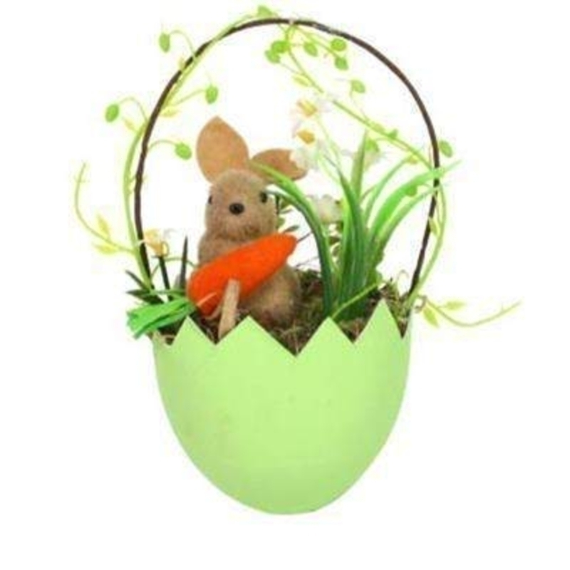 Easter bunny holding carrot sitting in an egg with articial moss and flowers. Ideal for hanging upon an easter tree. By the designer Gisela Graham who designs unique Easter decorations. (LxWxD) 18x9x8cm