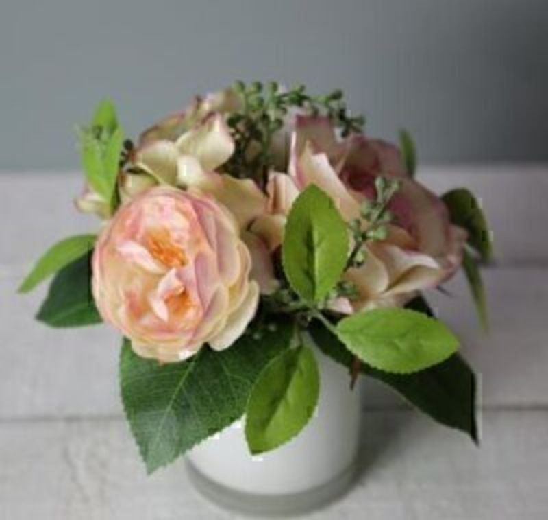 Peach Cream Artificial Rose Flower Arrangement in pot by Bloomsbury. White Glass Pot. Can also be called silk flowers the quality of these artificial flowers by Bloomsbury is second to none. For Realistic fake or silk flowers Bloomsbury are the perfect