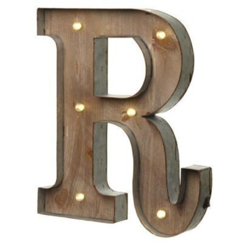 This R Sign With LED Lights by Heaven Sends could be paired with other letters to create a bespoke initial sign for a couple and or to be displayed on its own. Large in size this R sign has got LED lights and a switch on the side to turn it on. Made from wood and metal. Size: 35x5x41cm